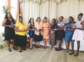 Recipients of the GNA awards, from left, Michelle Lewis, Ruth Hinds, Dawn Dunn, and Rhonda Mingo, Shaunette Waterman, Cedina Forde and Renee Hutson flank Chief Nursing Officer Tarramattie Barker and GNA President Joan Stewart (fourth and fifth from left) as they display their tokens.