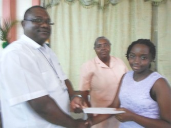 Owen John, Deputy Director of Nursing Services presents a bursary to Lisa Douglas (right) for her excellent performance at the NGSA as her mother, Veronica Douglas,  senior Health Visitor at the Ministry of Health looks on.