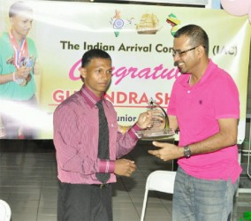 Minister of Natural Resources and the Environment, Robert Persaud rewards Gumendra Shewdas with a plaque for his historic feat at  the World Sub Juniors and Juniors Championships in Killeen, Texas last month where he became Guyana's youngest world power lifting champion. (Orlando Charles photo)