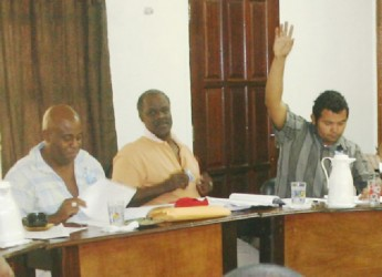 Douglas Gittens raises his hand to make a contribution during the September statutory meeting of the Regional Democratic Council, Region Ten, last Thursday. Also in picture are RDC Councillors Audwin Rutherford (left) and Leslie Gonsalves