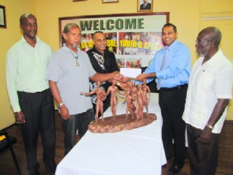Minister of Culture, Youth and Sport Dr. Frank Anthony (second from right) hands over the  cheque to sculptors Philbert Gajadhar (centre) and Winslow Craig (second from left), as Director of Culture, Dr James Rose (right) and Permanent Secretary Alfred King look on. (GINA photo)