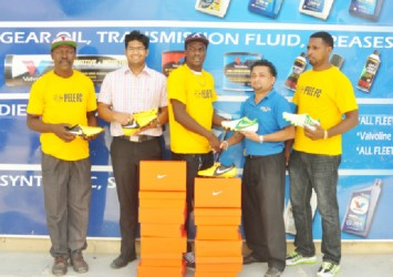Pele Captain Shemroy Arthur (centre) receives the football cleats from Sankars Auto Works Manager Jones Raghubar (right) while team coach Barry Myers (extreme left), Marketing Manager Shiv Sankar (second left), and club member Marvin Goodman (extreme right) look on.