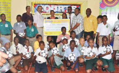 Managing Director of Courts Guyana Incorporated Clyde de Haas handing over sponsorship cheque to Petra Organization Co-Director Troy Mendonca as fellow executives and students from the participating schools look on.