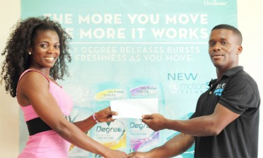 Alisha Fortune collects a sponsorship cheque from Vibert Gordon, a representative of DeSinco Trading to aid in purchasing her ticket to compete at the 41st annual Central American and Caribbean (CAC) Bodybuilding and Fitness Championships.