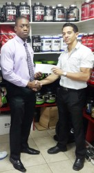 Mr. Guyana, Kerwin Clarke receiving his sponsorship cheque to cover his airfare to compete in the 41st annual Central American and Caribbean (CAC) Bodybuilding and Fitness Championships in the Dominican Republic from owner of Fitness Express, Jaime McDonald.