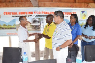 Timothy Daniels (left) receiving the keys to his new house from Permanent Secretary of the Ministry of Housing and Water, Emile McGarrel (GINA photo)