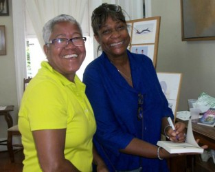 Maureen Marks-Mendonca (right) autographing a copy of her book for a fan.