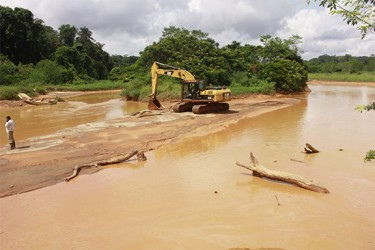 An excavator for mining crossing the silted Konawaruk River recently