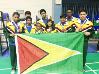 Members of the Guyana national badminton team which placed fourth at the just concluded Caribbean regional Badminton Confederation championships in Puerto Rico display the Guyana flag and their medals.