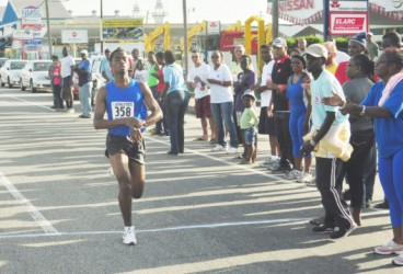 Cleveland Forde stops his watch after successfully defending his title yesterday morning at the Neal and Massy Group of Companies AinLim 10k road race. (Orlando Charles photo)