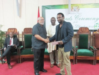 Ruel Johnson  (right) receiving his prize from President Donald Ramotar. At centre is UG Vice-Chancellor Jacob Opadeyi.