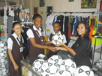 Receiving balls on behalf of the club from Store Manager Romona Arthur is Aaliyah Stanley while team mates Shaunna Taylor (left) and Cindy McPherson look on.