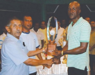 GFSCA organiser Wayne Jones (right) receiving tournament trophies from Ramchand Ragbeer.