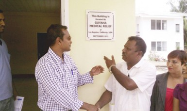 GMR Inc chief officer Sharir Chan (left) and Region Two Chairman Parmanand Persaud shake hands, while another representative looks on, after unveiling a plaque to mark the presentation of a newly-built VIA clinic at Charity.