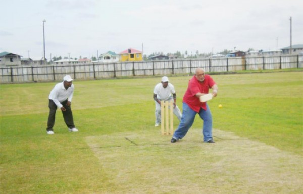 President Donald Ramotar hits the opening ball of a game at the Enmore Community Centre Ground for four.