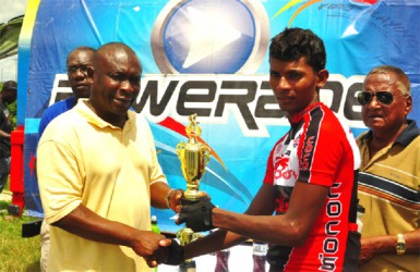 Winner! National Road Race champion, Raynauth Jeffrey receiving his trophy from Banks DIH's Communications Officer Troy Peters after emphatically winning yesterday's Powerade 50-mile road race. (Orlando Charles photo)