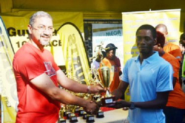 Guyana's best 10k road runner Cleveland Forde receives his first place prize from Clyde De Haas, Courts Managing Director.