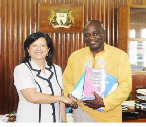 UG Vice Chancellor Prof Jacob Opadeyi and Dr Michele Ming shake hands as he displays some of the books donated to the university.