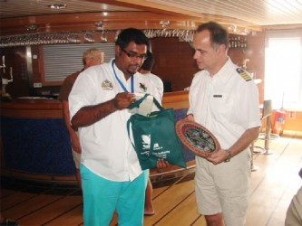 Minister of Tourism Irfaan Ally presents Captain of the National Geographic Explorer cruise ship Oliver Kruess with a token.