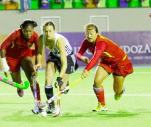 Argentina's Carla Rebecchi (centre) battling Guyana's Ulrica Sutherland (left) and Marzana Fiedtkou for possession of the ball during their team's 22-0 defeat of Guyana on Tuesday at the PAHF Cup. (See story on page 26)