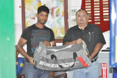 GCC president Lionel Jaikaran (right) hands over the cricket equipment to Robin Bacchus
