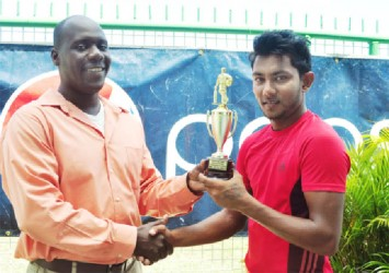 Man of the match Devendra Bishoo (right) receives his trophy from match referee Colin Stuart. (Orlando Charles photo)
