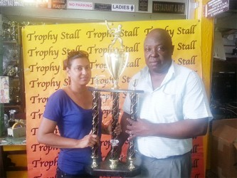 Devi Sunich, wife of Managing Director of Trophy Stall,Ramesh Sunich (left), hands over the first place trophy to first vice-president of the GSCL Inc Ian John.