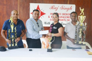 President of the DCB and proprietor of Raj Singh Insurance Brokers Raj Singh (second left) hands over the sponsorship cheque to DCB administrator Melinda Bishundyal. East Bank Demerara cricket coordinator Deonarayan Debidial (right) and DCB Marketing Manager Ray Persaud display the trophies.