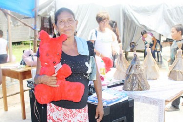 A woman displays a stuffed toy she made