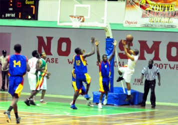 Albouystown/Charlestown's Sheldon Thomas shooting over Werk-en-Rust/Wortmanville duo of Joslyn Crawford (number 12) and Michael Turner (number 8) in the first game of the best of three finals Friday night at the Cliff Anderson Sports Hall.