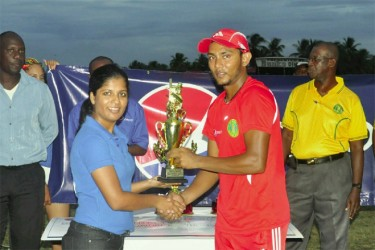 Devendra Bishoo receives the man of the match trophy. (Orlando Charles photo)