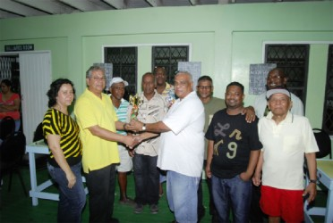 Proprietor of Living Clean Grocery and Variety Store Ramao Paul (left) hands over the winning trophy to skipper Edmond Sammy of Sammy's Six in the presence of other team members. Paul's wife Charmayne Paul is on his right.