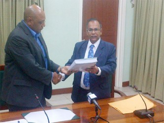 Auditor General Deodat Sharma (right) presents House Speaker Raphael Trotman with the 2012 Auditor's Report