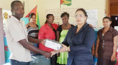 BBCI Administrative Assistant Bibi F Alli (second, right) handing over a television set, a DVD player and a voltage regulator to Sheet Anchor Nursery School.