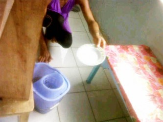 A parent bailing water out of the flooded classroom using a plate