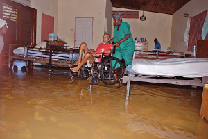 A nurse assists a resident of GH&DD's Sanctuary—Home for the Elderly in Chuma Monka Avenue in Diego Martin yesterday morning as flood waters swamped the ground floor of the establishment. Several residents were transferred to higher ground on the compound.