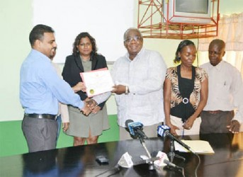 Chairman of the Board of Industrial Training, Clinton Williams (third from left) handing over the Apprenticeship licence to Barama's Head of Corporate Affairs and Forest Planning,  Mohindra Chand. (GINA photo)