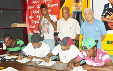 Some of the boxers that will take the ring on the 30th edition of the Guyana Fight Night Pro Am card on October 30 affixing their signature to their respective contracts yesterday. From right is Richard Williamson, Dexter Marques,Kishawn Simon, Edmond Declou (standing) and David Thomas (Orlando Charles photo)