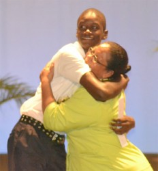A student of Plaisance Secondary hugs his teacher in appreciation for her efforts (GINA photo)
