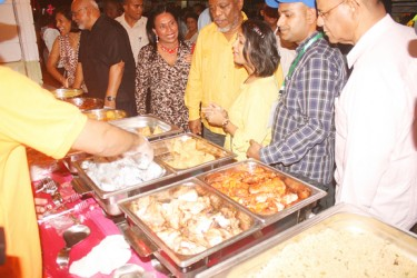 President Donald Ramotar and First Lady Deolatchmee Ramotar (far left), Prime Minister Sam Hinds and his wife Yvonne and others sampling food from the Aagman restaurant booth.