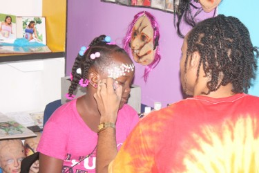 A representative from 'Tons of Fun Party Experience' face-paints a young girl.