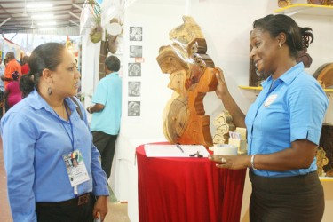 Jewellery box: Amanda Williams-Clarke (right) discusses her creative Map of Guyana jewellery box with  Nadia de Abreu at GuyExpo last night.
