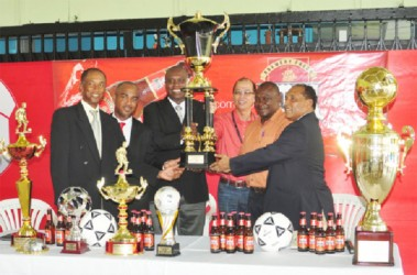 President of the Guyana Football Federation (GFF), Christopher Matthias, some executive members of the GFF and Banks DIH's Brian Choo-Hen and Troy Peters lifts the winner's trophy following yesterday's launch at the Banks DIH Limited Sports Club. (Orlando Charles photo)