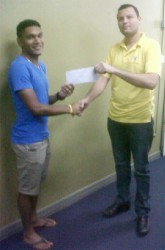 National cyclist, Alanzo Greaves receiving his sponsorship cheque from Accountant of Bounty Farm Limited, Roger Perriera to aid in purchasing a pair of Zipp 404 Carbon Wheels.