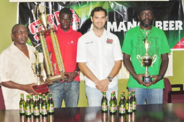 Brand Manager of Stag Beer, John Maikoo (centre) poses with the representatives of the BV/Triumph, Buxton United and the Mahaica Determinators following the distribution of cheques and trophies yesterday. (Orlando Charles photo)