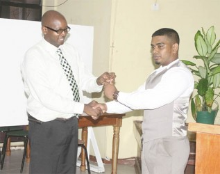 UG's Internal Auditor Quincy Bourne (left) handing over the keys of the University of Guyana Student Society's office to newly-elected president Richard Rambarran on Friday. (Photo by Arian Browne)