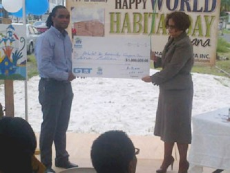 HfHG National Director Rawle Small (left) collects the symbolic cheque for $1 million from a GT&T representative