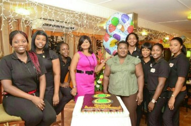 In photo: Nisa Walker (fourth from left) and some of her staff members pose with the anniversary cake
