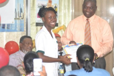 Postmaster General, Henry Dundas presenting an award to the top CSEC student of St. Rose's High School (GINA photo)