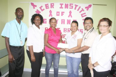 Dr. Narendra Bhalla (second from right) receiving the cheque from a representative of the Avon Community Help Fund yesterday at the Cancer Institute of Guyana. (Photo by Arian Browne)